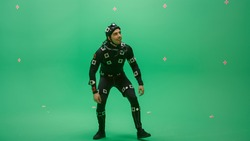 Actor Wearing Motion Caption Suit and Head Rig acts as an Animal or a Monster for CGI Green Screen Scene. Big Budget Filmmaking On Film Studio Set Shooting Blockbuster Movie with Chroma Key