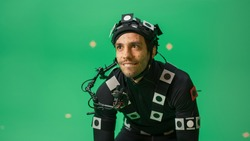 Actor Wearing Motion Caption Suit and Head Rig acts as an Animal or a Monster for CGI Green Screen Scene. Filmmaking On Film Studio Set Shooting Blockbuster Movie with Chroma Key.