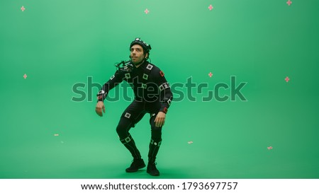 Actor Wearing Motion Caption Suit and Head Rig acts as an Animal or a Monster for CGI Green Screen Scene. Big Budget Filmmaking On Film Studio Set Shooting Blockbuster Movie with Chroma Key Сток-фото ©