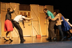 Actors and actresses play comedic roles in a show performance on a theater stage.