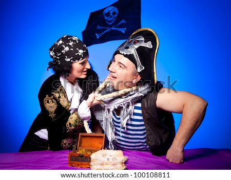 actors in a suits of the pirates are fighting near the map and treasures  on a blue background