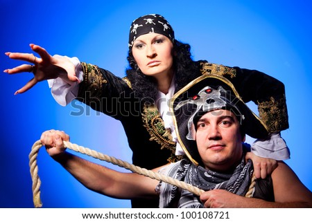 actors in a suits of the pirates with a cocked hat and a rope on a blue background