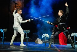 Actors in black and white clothes with woman in red dress play a duel with swords performance on the theater stage