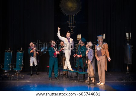 Actors, men in old clothes frock coats and uniforms and women in medieval dresses with lush skirts posing on stage in the background of scenery