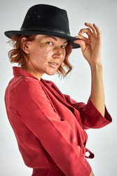 actress woman in black hat posing at camera in studio, wearing elegant red dress outfit