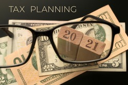 Actual concept for business, finance, banking, budgeting, economic topics. Glasses, number 2021, Tax planning text, dollar banknotes background. Selective focus