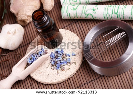 Acupuncture needles laying on the stone mat, moxa sticks on wooden desk and lavender petals with macerated oil. TCM Traditional Chinese Medicine concept photo
