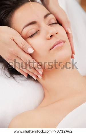 Acupuncture needles on head of a young woman at the spa