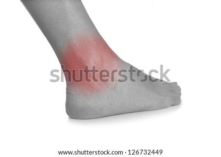 Acute pain in a woman ankle. Female holding hand to spot of ankle-ache. Concept photo with Color Enhanced blue skin with read spot indicating location of the pain.
