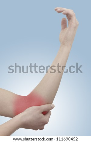 Acute pain in a woman elbow. Female holding hand to spot of elbow pain. Concept photo with Color Enhanced skin with read spot indicating location of the pain.