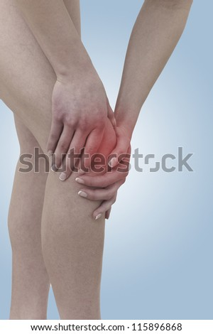 Acute pain in a woman  knee. Female holding hand to spot of knee-aches. Concept photo with Color Enhanced skin with read spot indicating location of the pain.