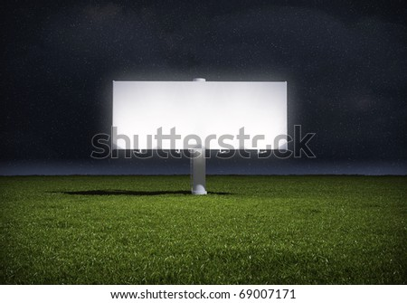 Ad billboard standing in a field of grass - night version