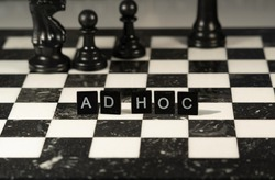 Ad Hoc (latin for when needed)  concept represented by black and white letter tiles on a marble chessboard with chess pieces
