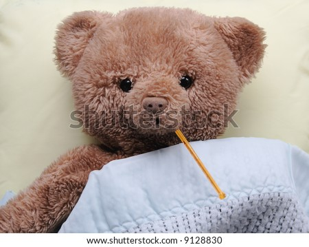 ad teddy bear on a pale yellow pillow with a thermometer in its mouth and covered by a blue baby blanket