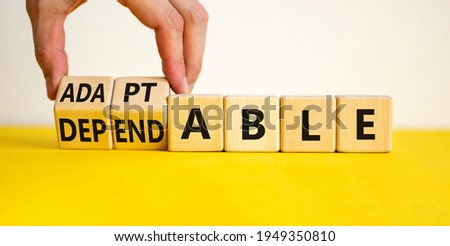 Adaptable or dependable symbol. Businessman turns wooden cubes and changes the word dependable to adaptable. Beautiful white background, copy space. Business and adaptable or dependable concept. Photo stock ©