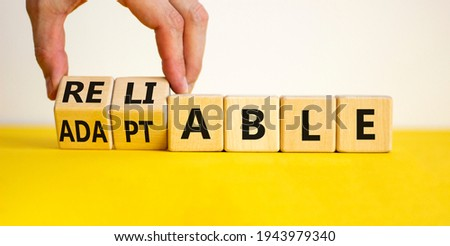 Adaptable or reliable symbol. Businessman turns wooden cubes and changes the word adaptable to reliable. Beautiful white background, copy space. Business and adaptable or reliable concept. Foto d'archivio ©