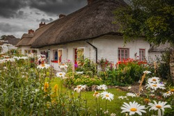 Adare, Ireland. Thatched cottage in the picturesque Village of Adare, Co. Limerick full of flowers in front garden. Ireland, Europe
