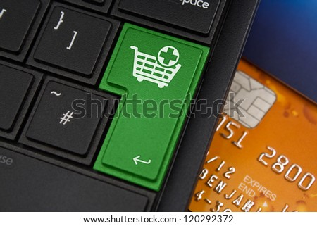 Add to Cart Enter Key on a modern laptop qwerty keyboard with bank smart card underneath to represent on-line shopping