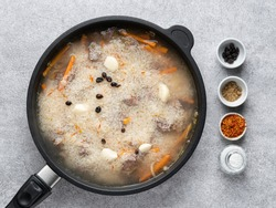 Add water and spices (saffron, cumin and barberry) to fried beef meat pieces, carrot sticks and onion in black skillet. Stew rice and meat. Step by step cooking process. Pilaf (pilau, plov).