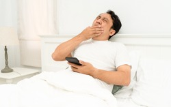 Addict man sleeping on home holding mobile phone in his hand in. Social media overuse ddiction and obsession concept.