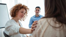 Addicted people comforting woman at psychotherapy session. Support gesture. Woman comforting woman patient at group rehub meeting. Rear view at upset woman feel depression get psychological support