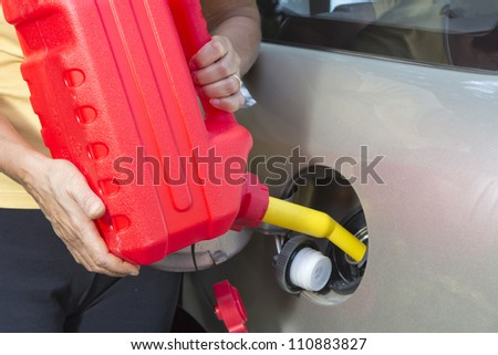 Adding fuel in car with Red Plastic Gas can (fuel container)-closeup