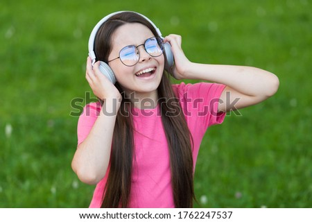 Adding happiness through singing. Happy singer sing song on green grass. Little girl enjoy singing in headphones. Singing voice. Vocal exercises. Summer music. Enjoying solo singing.