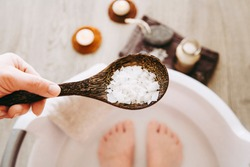 Adding Magnesium Chloride vitamin salt in foot bath water, solution. Magnesium grains in foot bath water are ideal for replenishing the body with this essential mineral, promoting overall well being.
