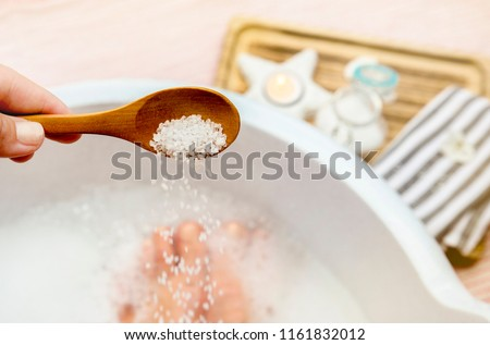 Adding Magnesium Chloride vitamin salt in foot bath water, solution. Magnesium grains in foot bath water are ideal for replenishing the body with this essential mineral, promoting overall wellbeing. Stock photo ©