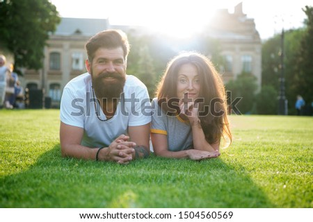 Adding some romance. Holiday romance of bearded man and sexy woman. Couple in love relaxing on green grass on sunny summer outdoor. Feeling romance. Love and romance. #1504560569