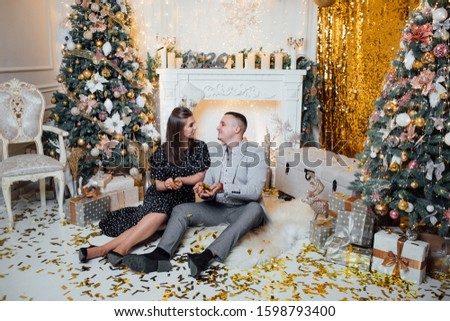 Adding some romance. Holiday romance of man and sexy woman. Couple in love relaxing in the studio. Feeling romance. Love and romance. Christmas and New Year concept.