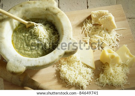 Adding the grated cheese to the preparation - stock photo