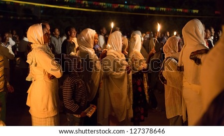 ADDIS ABABA, ETHIOPIA - JANUARY 19: A large crowd of people pray with candle light during Timket (baptism in Amharic) celebrations  on January 19, 2013 in Addis Ababa.