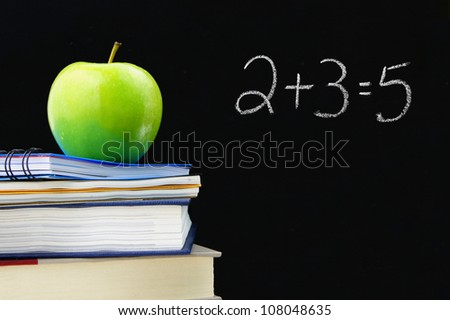 Addition equation written on a blackboard with books and apple in front