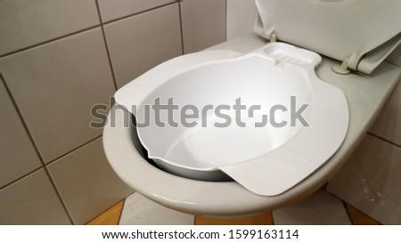 Additional bidet, medical device bowl for sitting baths, on the toilet. Stock fotó ©