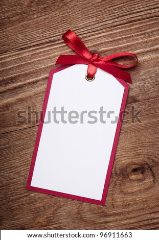 address card with bow on old wooden background.