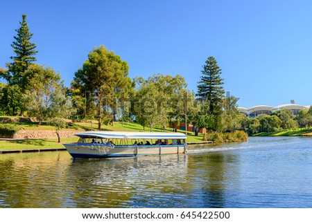 Adelaide, Australia - April 14, 2017: Iconic Pop-Eye boat with people on board traveling upstream  Torrens river in Adelaide CBD on a bright day #645422500