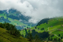 Adelboden panorama with alpine farmhouses and trees, forests and green meadows on a cloudy day. valley with holiday destination village in Swiss alps. interesting scenery with alpine weather mood