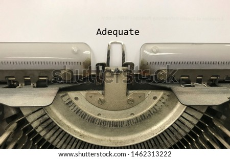 Adequate typed words on a vintage typewriter