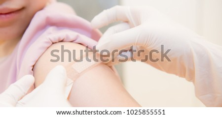 Adhesive bandage on arm after injection vaccine or medicine,ADHESIVE BANDAGES PLASTER - Medical Equipment,Soft focus Adhesive bandage on a female brachium after vaccination,