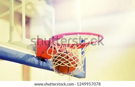 Adidas Basketball ball hitting basket in gym