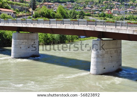 Adige River estuary with fresh water in Trentino Alto Adige and background forest and residential homes