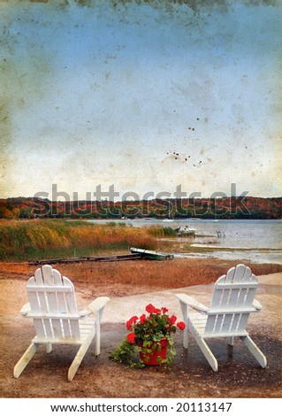 Adirondack chairs by the water on a grunge background in the fall.