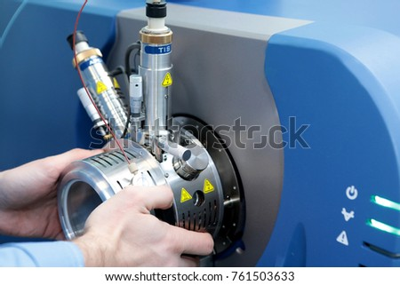 Adjust the mass spectrometer. The man analyzes the device for determining the masses of atoms. Device for the pharmaceutical industry. Ionic source of mass spectrometer.