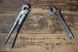 Adjustable and pipe wrenches on a wooden surface. Tool for car repair, plumbing. There is a copyspace. Selective focus, shallow depth of field