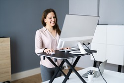 Adjustable Height Desk Stand In Office Using Computer