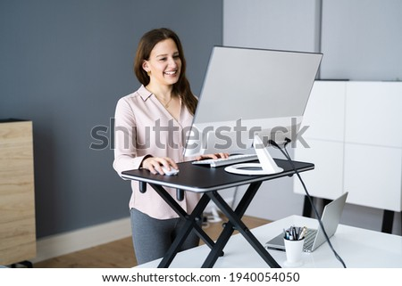 Adjustable Height Desk Stand In Office Using Computer Foto stock ©