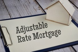 Adjustable Rate Mortgage wording with house model over a wooden background. Mortgage real estate property concept. Selective focus image