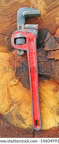 Adjustable spanner on wood background