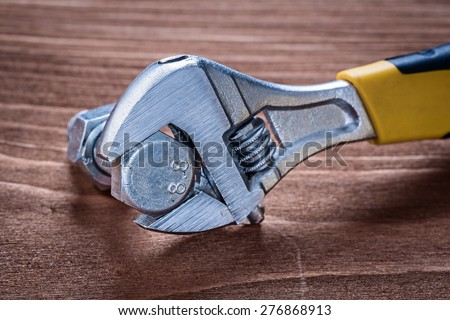 Adjustable spanner stainless bolt and screw nut on brown wooden board construction concept